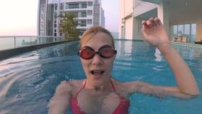 Jovem mulher alegre feliz na série vermelha da natação na piscina, acenando uma mão Câmera da ação vídeos de arquivo