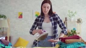 A jovem mulher alegre na camisa de manta passou o ferro de linho em casa, dançando perto acima video estoque