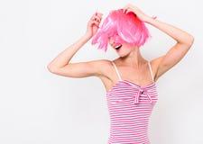 Jovem mulher alegre na peruca cor-de-rosa e dança no fundo branco Fotos de Stock Royalty Free
