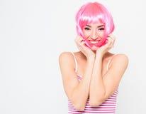Jovem mulher alegre na peruca cor-de-rosa e levantamento no fundo branco Fotografia de Stock Royalty Free