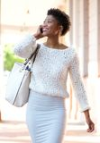Jovem mulher alegre que anda e que chama pelo telefone celular Fotografia de Stock