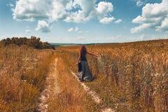 Jovem mulher alegre que anda pela estrada do campo foto de stock royalty free