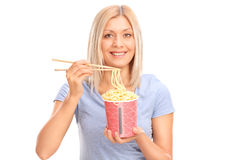 Jovem mulher alegre que come macarronetes foto de stock