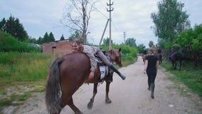 Jovem mulher alegre que encontra-se no cavalo que anda através da estrada rural vídeos de arquivo