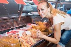 Jovem mulher alegre que escolhe as peças frescas da galinha Imagens de Stock Royalty Free