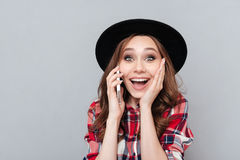 Jovem mulher alegre que está sobre a parede cinzenta que fala pelo telefone Imagens de Stock Royalty Free
