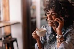 Jovem mulher alegre que fala no telefone em um café Fotos de Stock