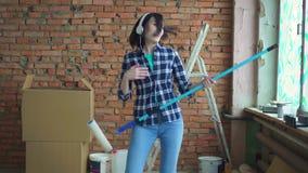 Jovem mulher alegre que faz os reparos, jogando uma guitarra convertível video estoque