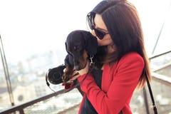 Jovem mulher alegre que guarda seu cão pequeno ao beijá-lo na rua imagens de stock