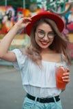 Jovem mulher alegre que guarda uma bebida ao sorrir imagens de stock royalty free