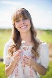 Jovem mulher alegre que guardara o dente-de-leão Fotos de Stock