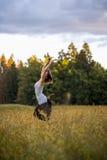 Jovem mulher alegre que pula em um prado Foto de Stock Royalty Free