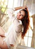 Jovem mulher alegre que senta-se no peitoril da janela Fotografia de Stock Royalty Free