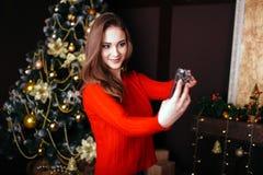 Jovem mulher alegre que toma um selfie do Natal com smartphone Imagem de Stock