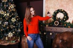 Jovem mulher alegre que toma um selfie do Natal com smartphone Fotos de Stock Royalty Free