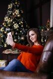 Jovem mulher alegre que toma um selfie do Natal com smartphone Foto de Stock Royalty Free