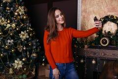 Jovem mulher alegre que toma um selfie do Natal com smartphone Imagem de Stock Royalty Free