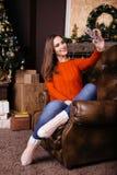 Jovem mulher alegre que toma um selfie do Natal com smartphone Fotos de Stock