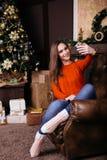 Jovem mulher alegre que toma um selfie do Natal com smartphone Imagens de Stock