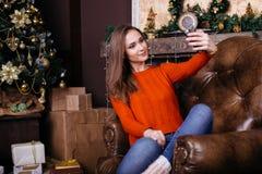 Jovem mulher alegre que toma um selfie do Natal com smartphone Foto de Stock