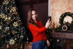 Jovem mulher alegre que toma um selfie do Natal com smartphone Fotografia de Stock
