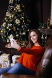 Jovem mulher alegre que toma um selfie do Natal com smartphone Imagens de Stock Royalty Free