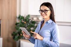 Jovem mulher alegre que usa sua tabuleta imagens de stock