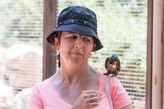A jovem mulher alimenta papagaios no jardim zoológico australiano Gan Guru nos kibutz Nir David, em Israel Foto de Stock Royalty Free