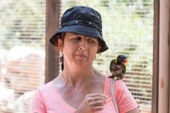A jovem mulher alimenta papagaios no jardim zoológico australiano Gan Guru nos kibutz Nir David, em Israel Fotografia de Stock Royalty Free