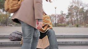 Jovem mulher amável que dá o dinheiro ao homem desabrigado pobre que implora pela ajuda na rua vídeos de arquivo