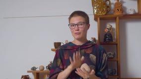 A jovem mulher amassa a argila em suas mãos video estoque