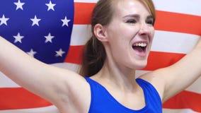 Jovem mulher americana Celebrates que guarda a bandeira dos EUA no movimento lento imagens de stock
