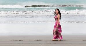 A jovem mulher anda com os pés descalços ao longo da costa do oceano Imagem de Stock Royalty Free