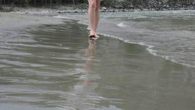 A jovem mulher anda na ressaca calma na praia video estoque