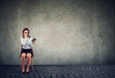 Jovem mulher ansiosa com o despertador que espera uma entrevista foto de stock royalty free