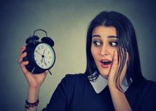 Jovem mulher ansiosa que olha o despertador Conceito da pressão de tempo imagens de stock royalty free