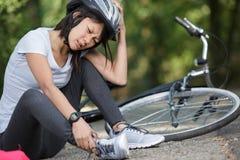 Jovem mulher ap?s a queda da bicicleta imagem de stock royalty free