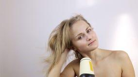 A jovem mulher após ter tomado um banho seca seu cabelo com um hairdryer filme