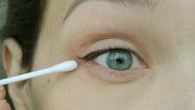 A jovem mulher apaga a parte adicional da seta Composição natural do olho em casa video estoque