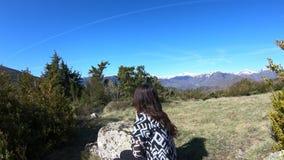 A jovem mulher apenas empoleirou-se em uma rocha observando as montanhas pirenaicas, França video estoque