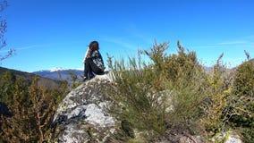 A jovem mulher apenas empoleirou-se em uma rocha observando as montanhas pirenaicas, França vídeos de arquivo