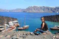A jovem mulher aprecia a vista de barcos da excursão no porto pequeno no volc Foto de Stock