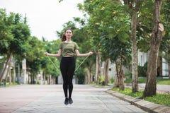 Jovem mulher apta com corda de salto em um parque fotografia de stock