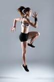 Jovem mulher apta e desportiva que corre no fundo branco fotos de stock