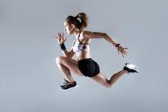 Jovem mulher apta e desportiva que corre no fundo branco fotos de stock royalty free