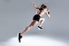 Jovem mulher apta e desportiva que corre no fundo branco fotografia de stock