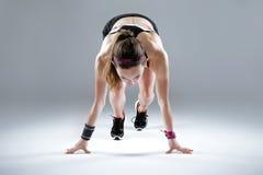 Jovem mulher apta e desportiva que prepara-se para uma corrida no backgrou branco imagens de stock royalty free