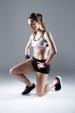 Jovem mulher apta e desportiva que prepara-se para uma corrida no backgrou branco foto de stock