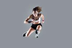 Jovem mulher apta e desportiva que salta no fundo branco fotos de stock royalty free