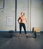 Jovem mulher apta no gym com barbell foto de stock royalty free